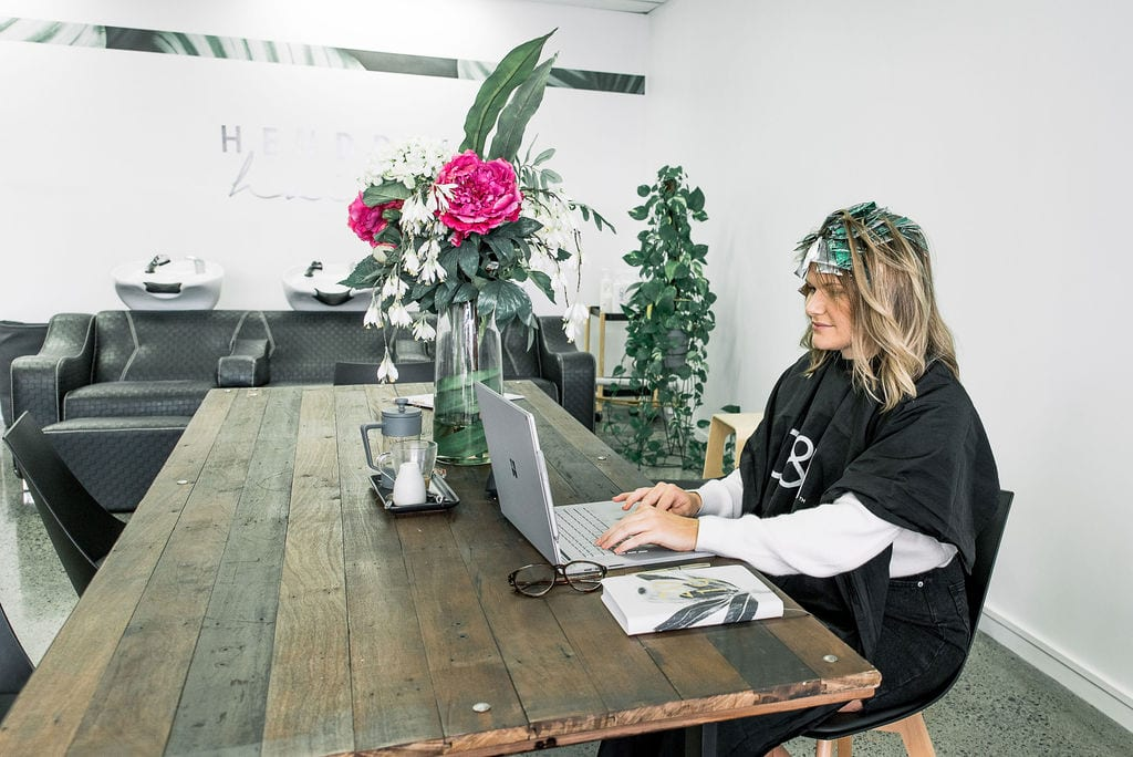 Woman working at computer at table with foils in hair
