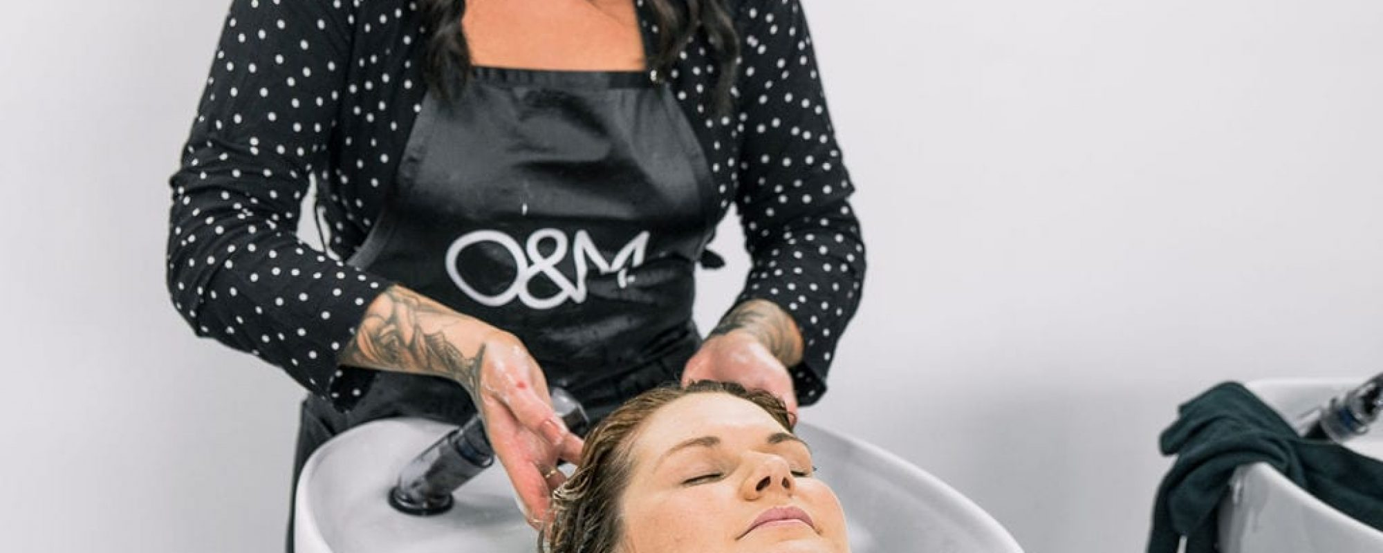 Woman having hair washed in salon basin